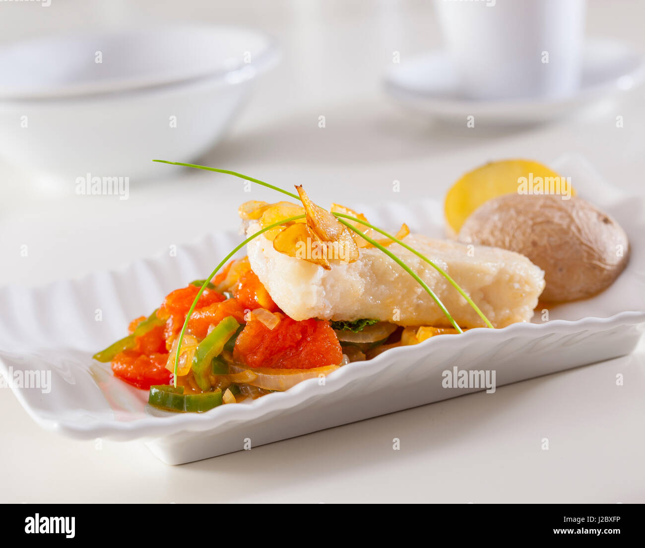 Grouper fillet served with fried garlic an vegetables. Stock Photo