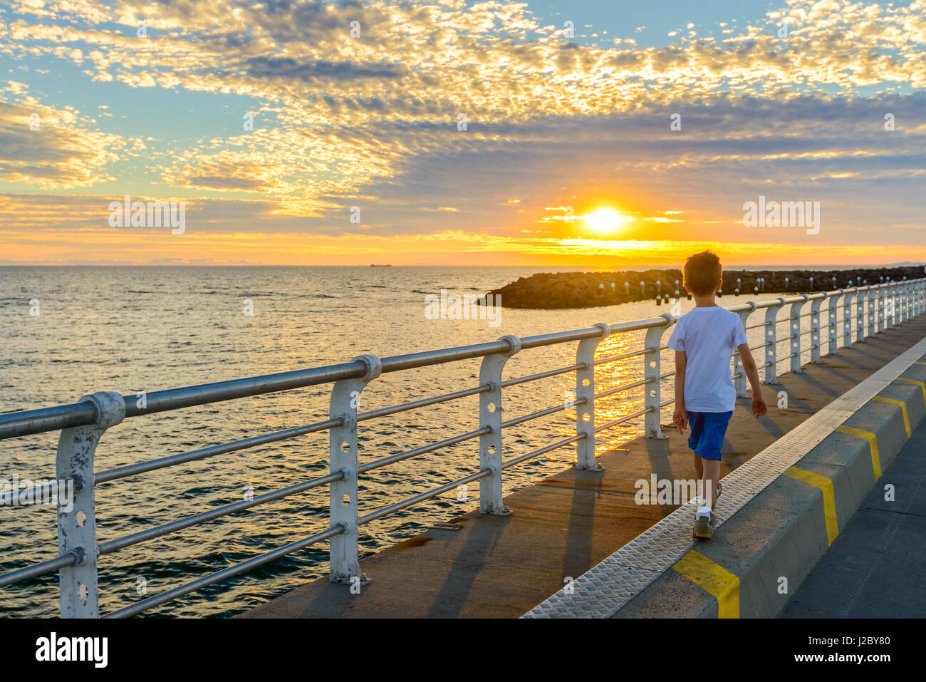 Boy walking along St. Kilda Jetty at sunset, Melbourne, Victoria, Australia - Stock Image