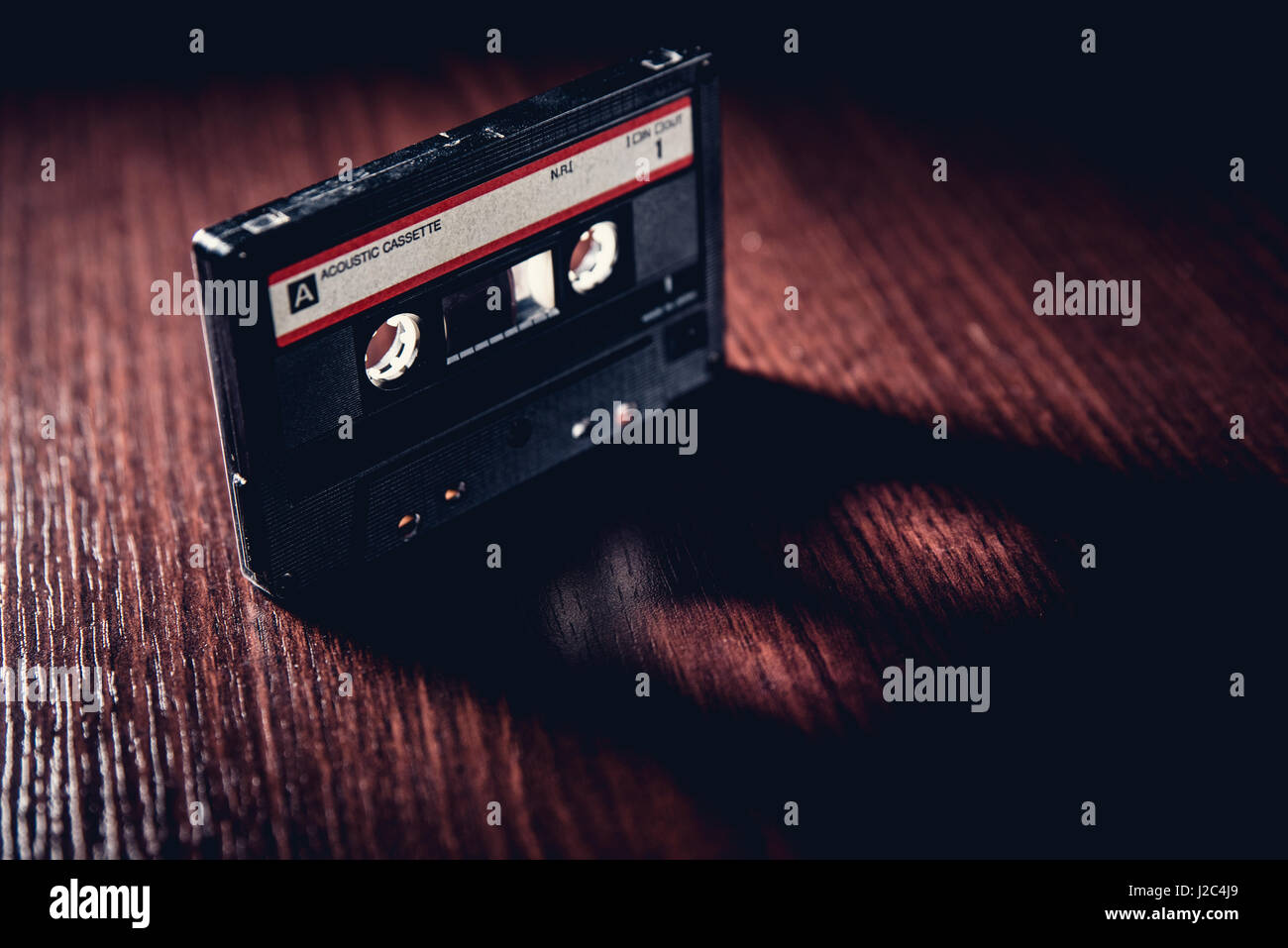 Old-fashioned cassette tape on the dark surface - Stock Image