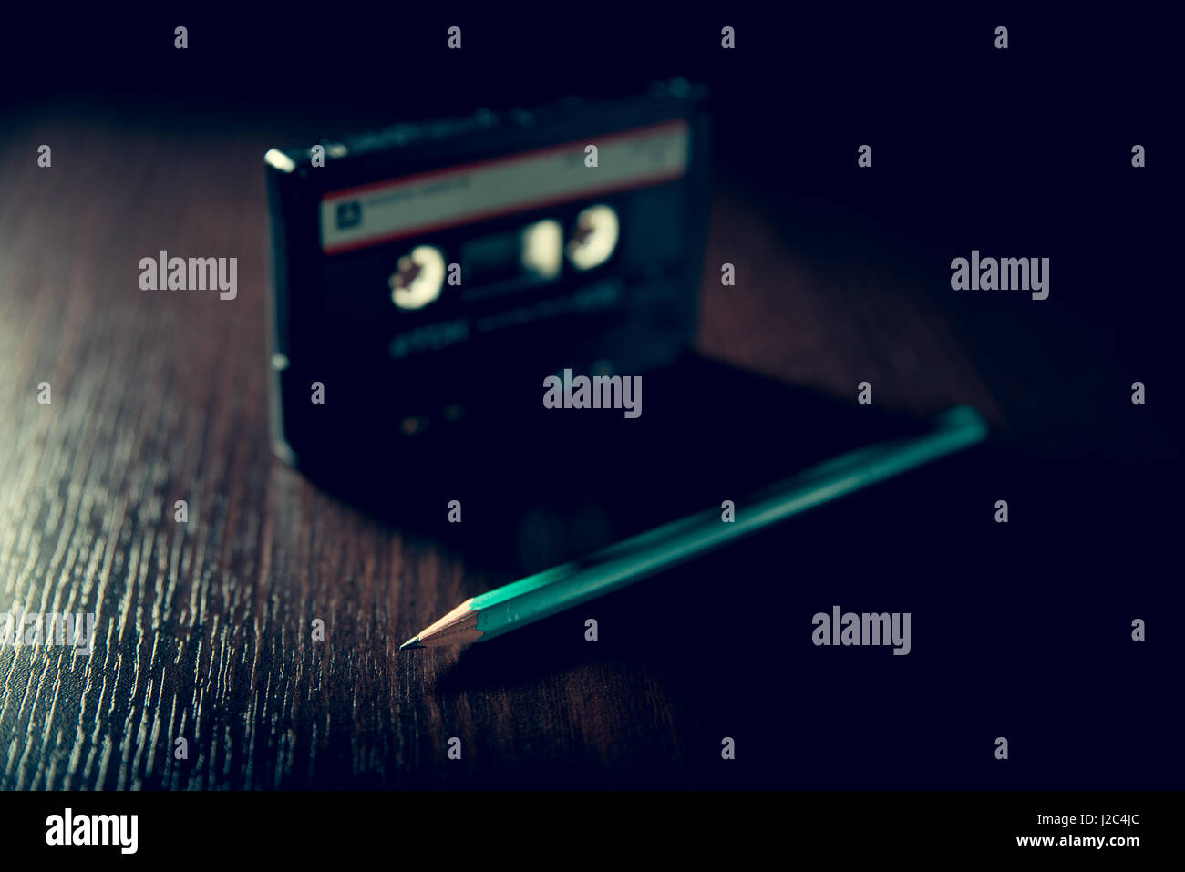 Old-fashioned cassette tape on the dark surface and green pencil - Stock Image