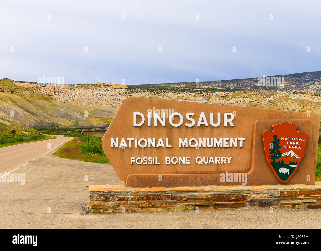 Jensen, USA - May 29, 2016: Entrance sign of the Dinosaur National Monument and the quarry that contains dinosaur - Stock Image