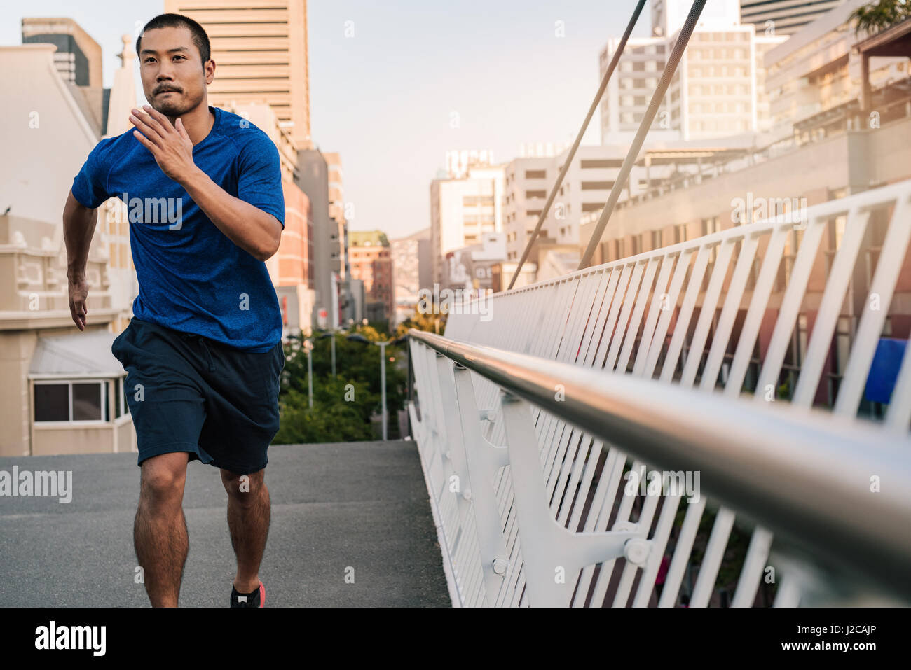 Athletic young Asian man running through the city - Stock Image