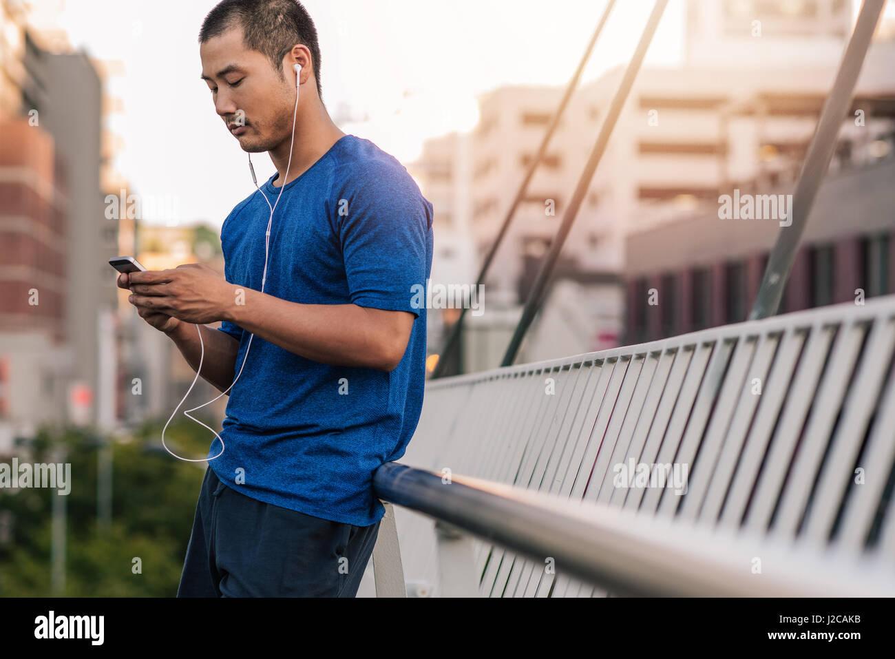 Sporty Asian man choosing music before a run - Stock Image