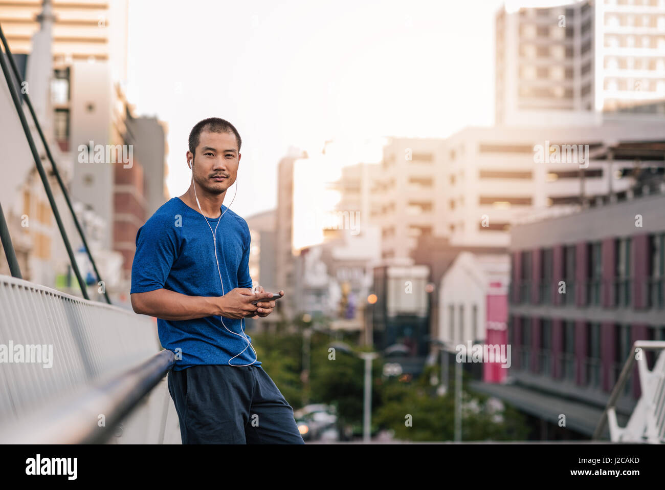 Young Asian man listening to music before a city run - Stock Image