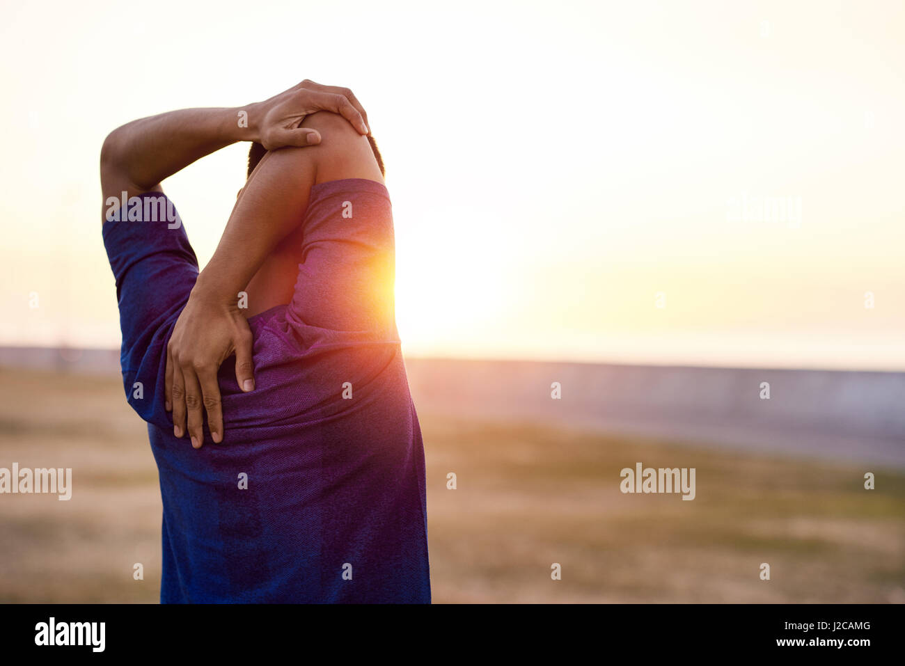 Fit young man stretching his shoulders before a morning run - Stock Image