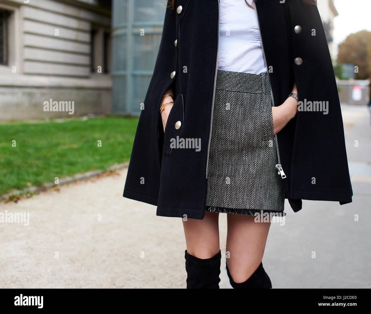 Woman in street wearing tweed miniskirt and black cape, crop - Stock Image