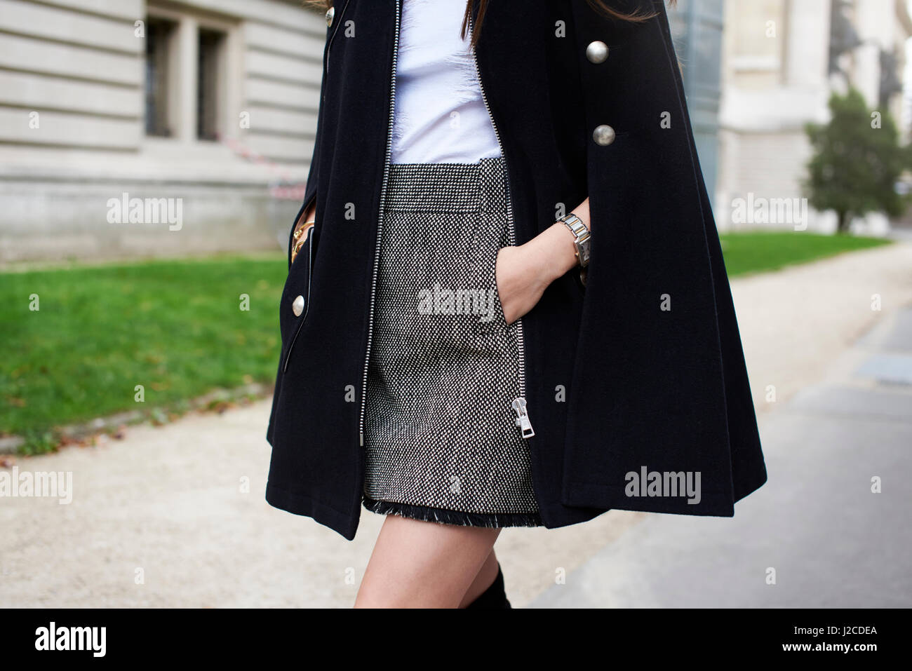 Woman wearing tweed miniskirt and black cape, side view crop - Stock Image