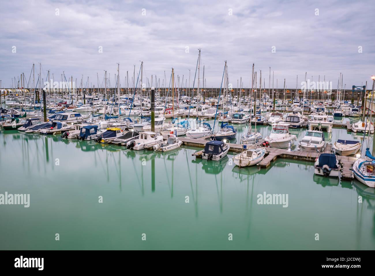 Boats, yachts, and fishing boats moored at Brighton Marina docs on a cloudy day. - Stock Image