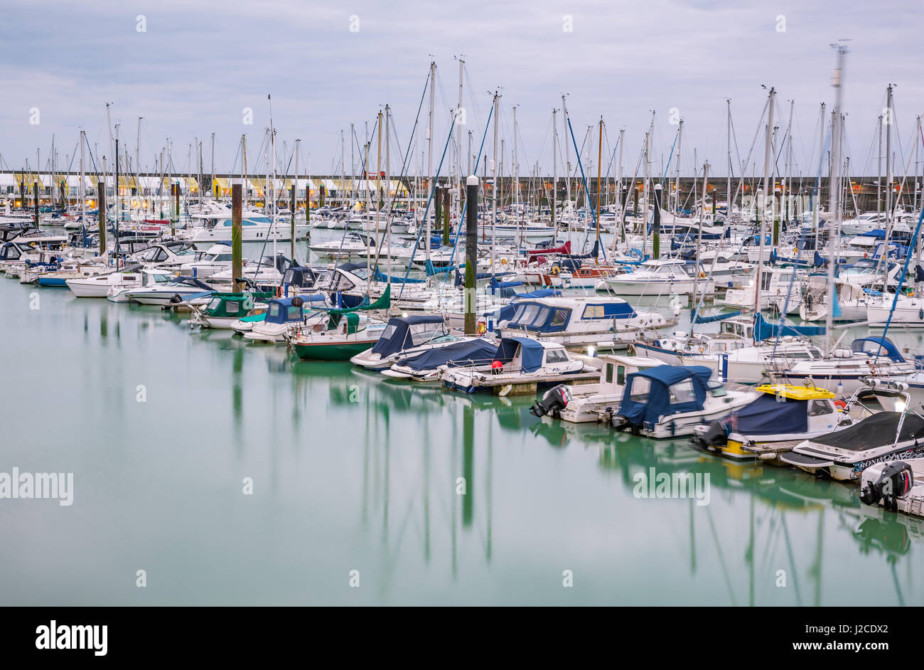 Boats, yachts, and fishing boats moored at Brighton Marina docs on a cloudy day. - Stock Image