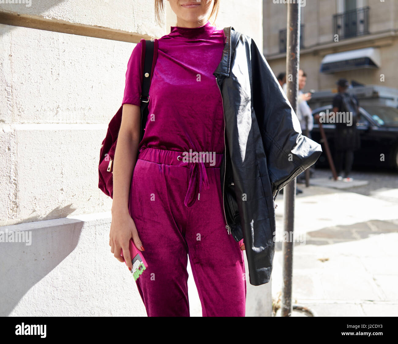 Woman in magenta top and track pants in street, crop - Stock Image