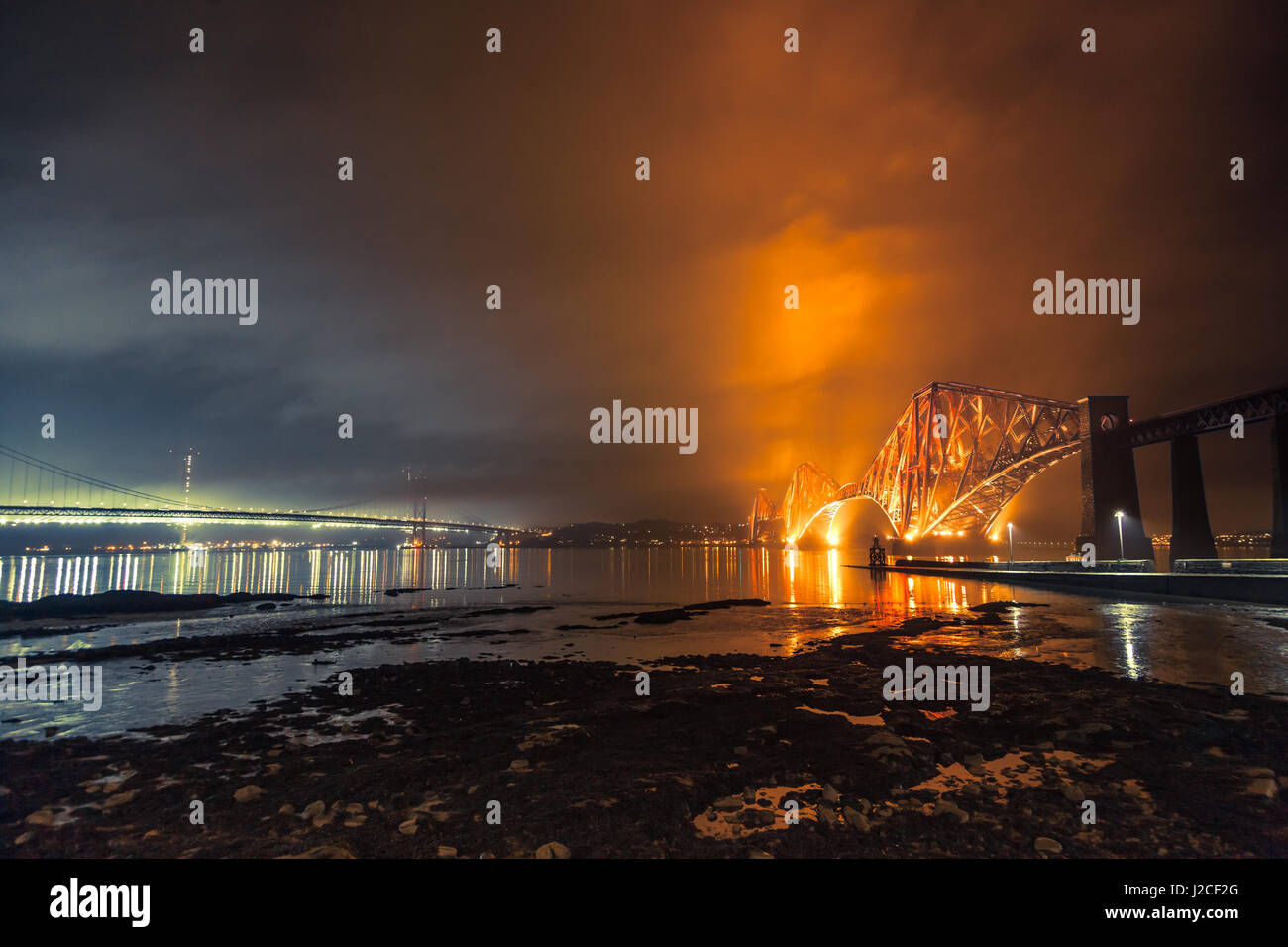 The Forth Rail Bridge and Forth Road Bridge crossings over the Firth River at night. South Queensferry, Edinburgh, Stock Photo