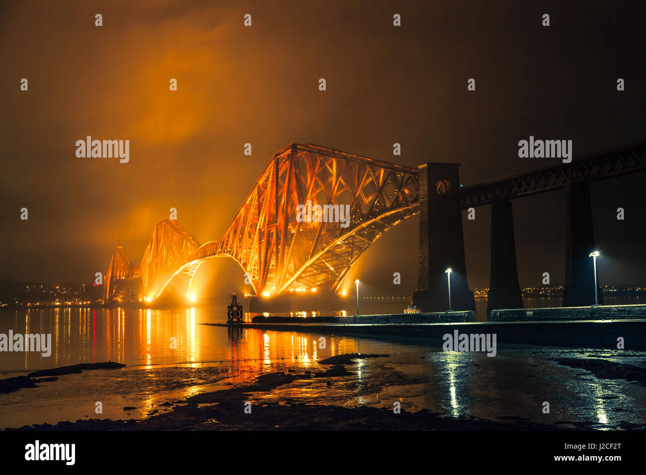 The Forth Rail Bridge lit up at night. Golden light shining in to the sky above. South Queensferry, Edinburgh, Scotland - Stock Image