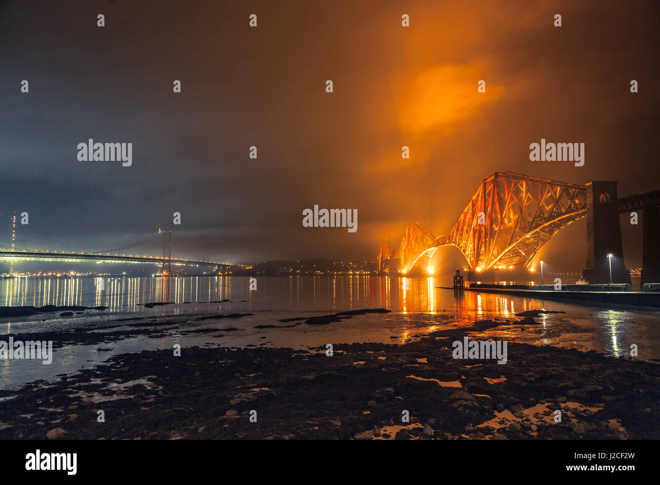 The Forth Rail Bridge lit up at night. Golden light hits the clouds above. South Queensferry, Edinburgh, Scotland - Stock Image