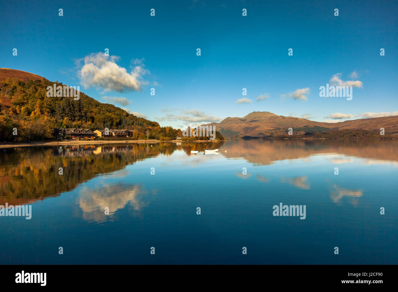 Clouds reflect in the calm waters of Loch Lomond on a clear sunny day. Luss, Scottish Highlands, Scotland. - Stock Image