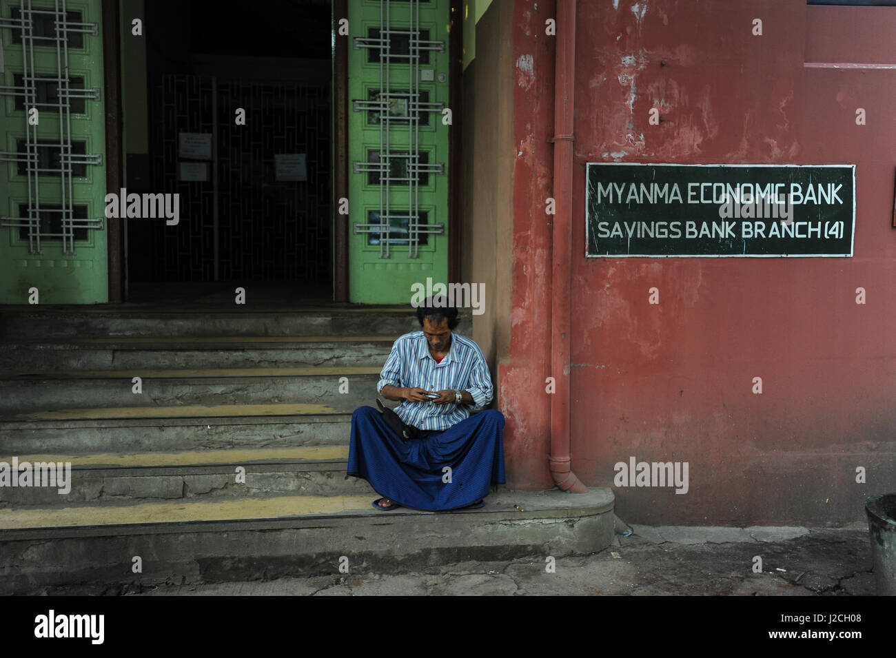 07.10.2013, Yangon, Republic of the Union of Myanmar, Asia - A man is seen sitting on the steps in front of a branch - Stock Image