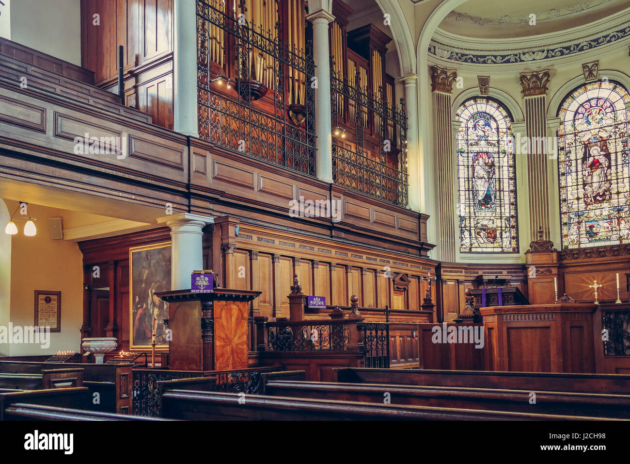 Saint Annes Church in Manchester, UK. Side view of benches, organ and beautiful mosaic windows Stock Photo
