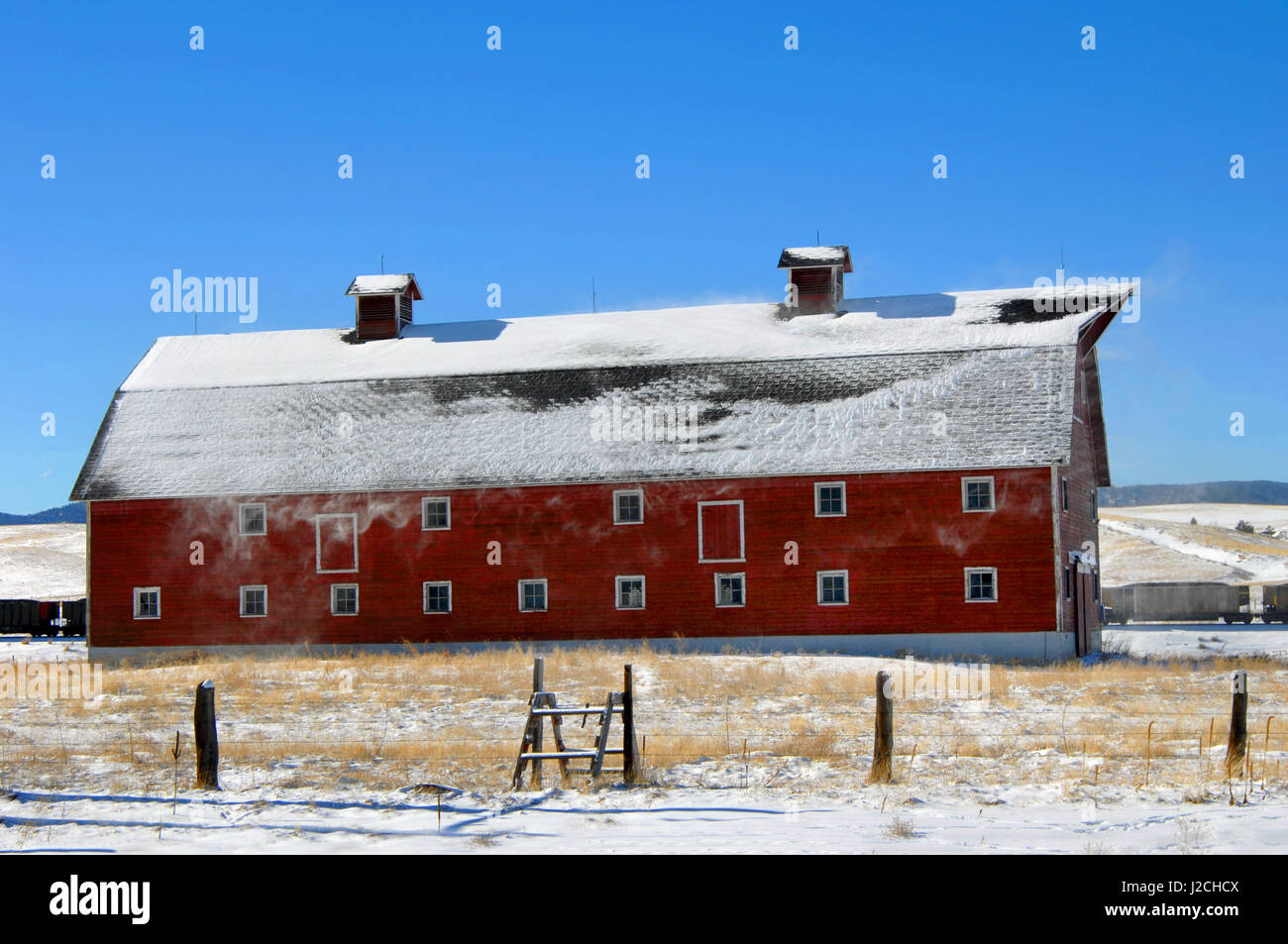 Snow blows from the rood of a red, wooden barn in a field in Colorado.  Coal train passes behind barn.  Barn is - Stock Image