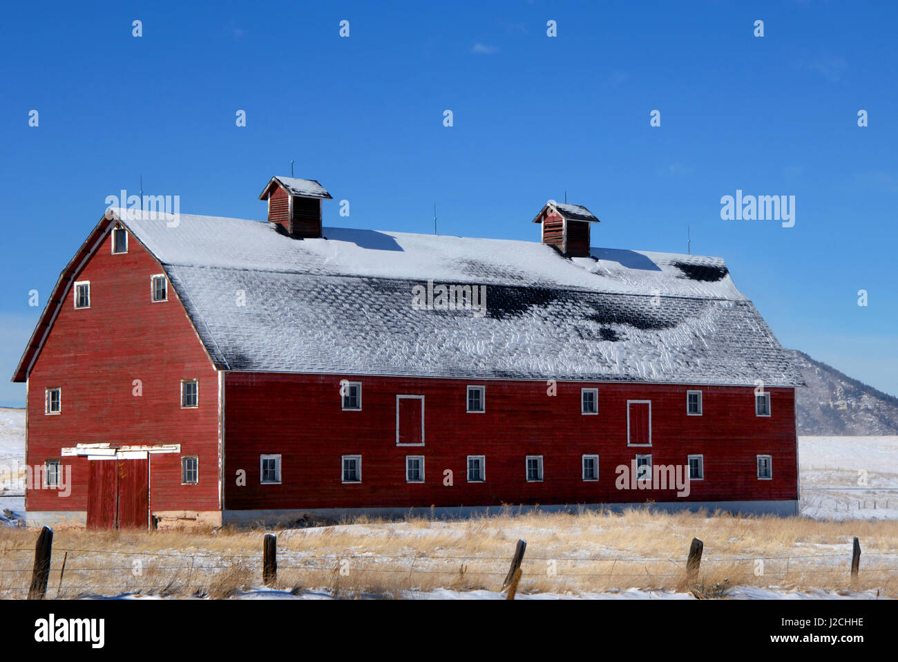 Old, red, wooden barn sits on a field in Colorado.  It is three story with dormers on top.  Light layer of snow - Stock Image