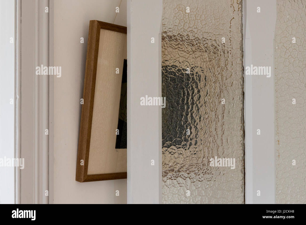 The view of a picture frame seen half directly and half through frosted glass - Stock Image