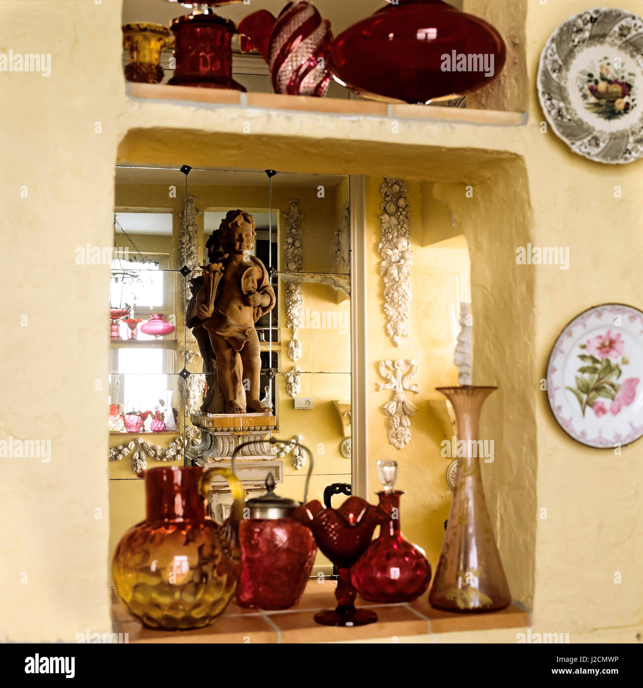 Yellow shelves with red vases. - Stock Image