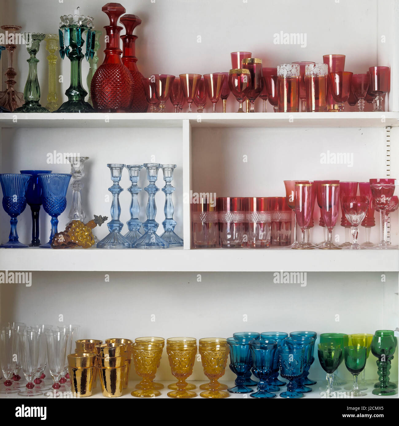 Shelves of colored glassware. - Stock Image