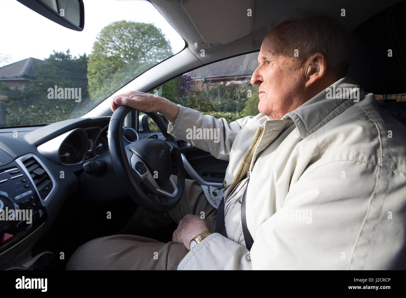 Elderly man in his eighties driving a car, England, UK - Stock Image