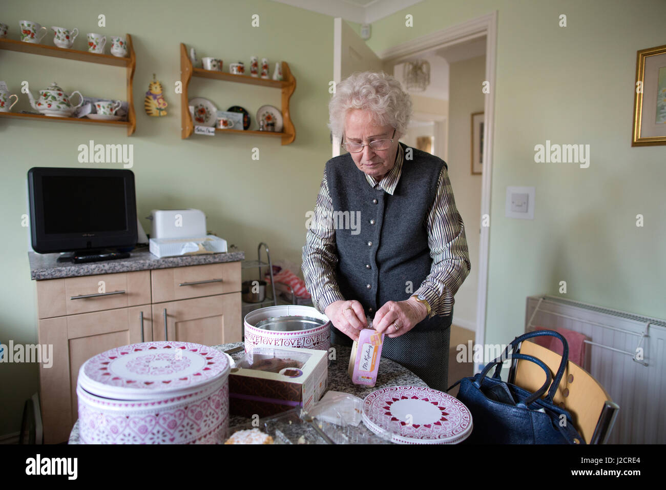 Elderly lady preparing an english teatime with various cakes on her kitchen table, England, United Kingdom - Stock Image