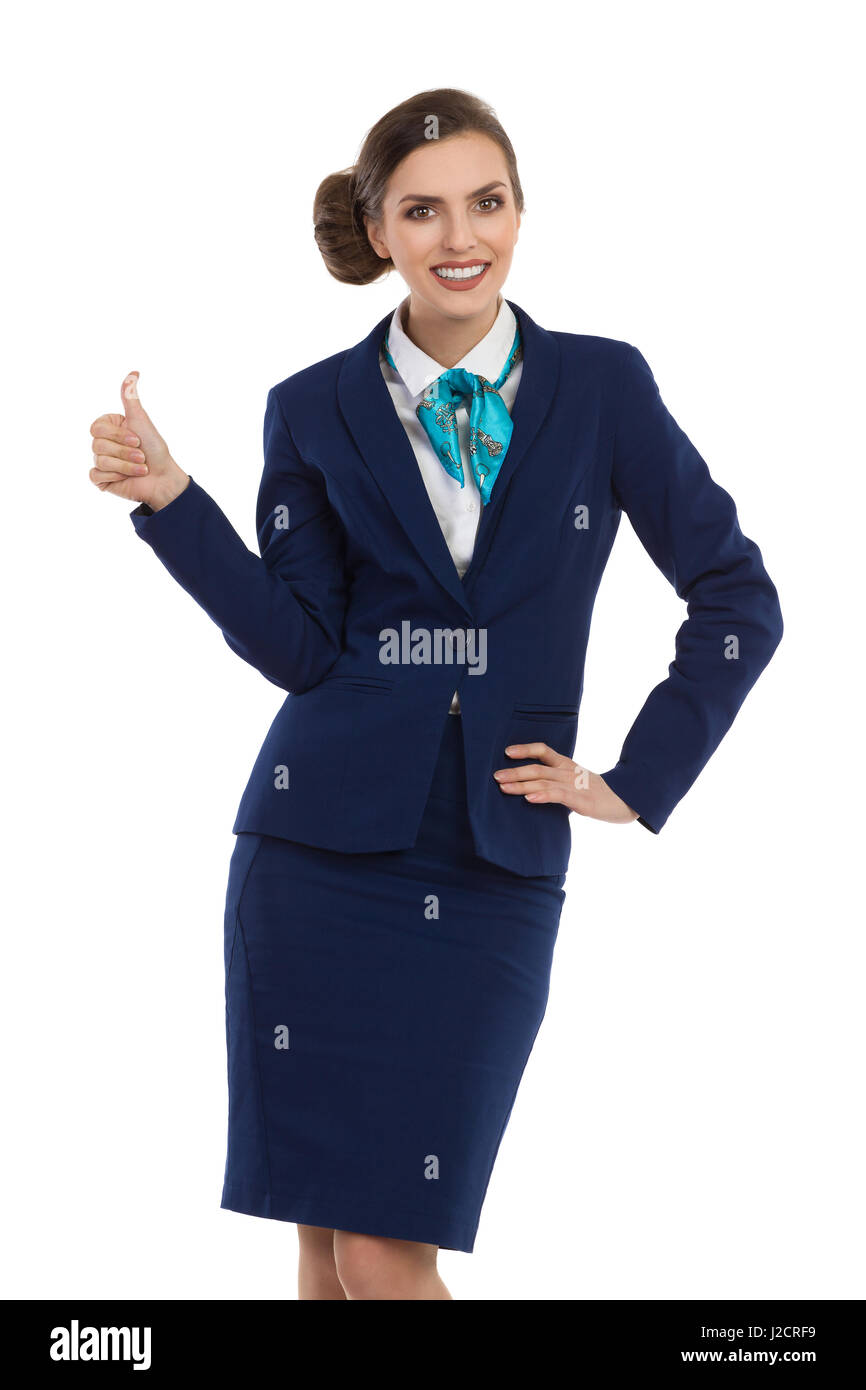 Smiling woman in blue suit and skirt standing with hand on hip, showing thumb up and looking at camera. Three quarter - Stock Image