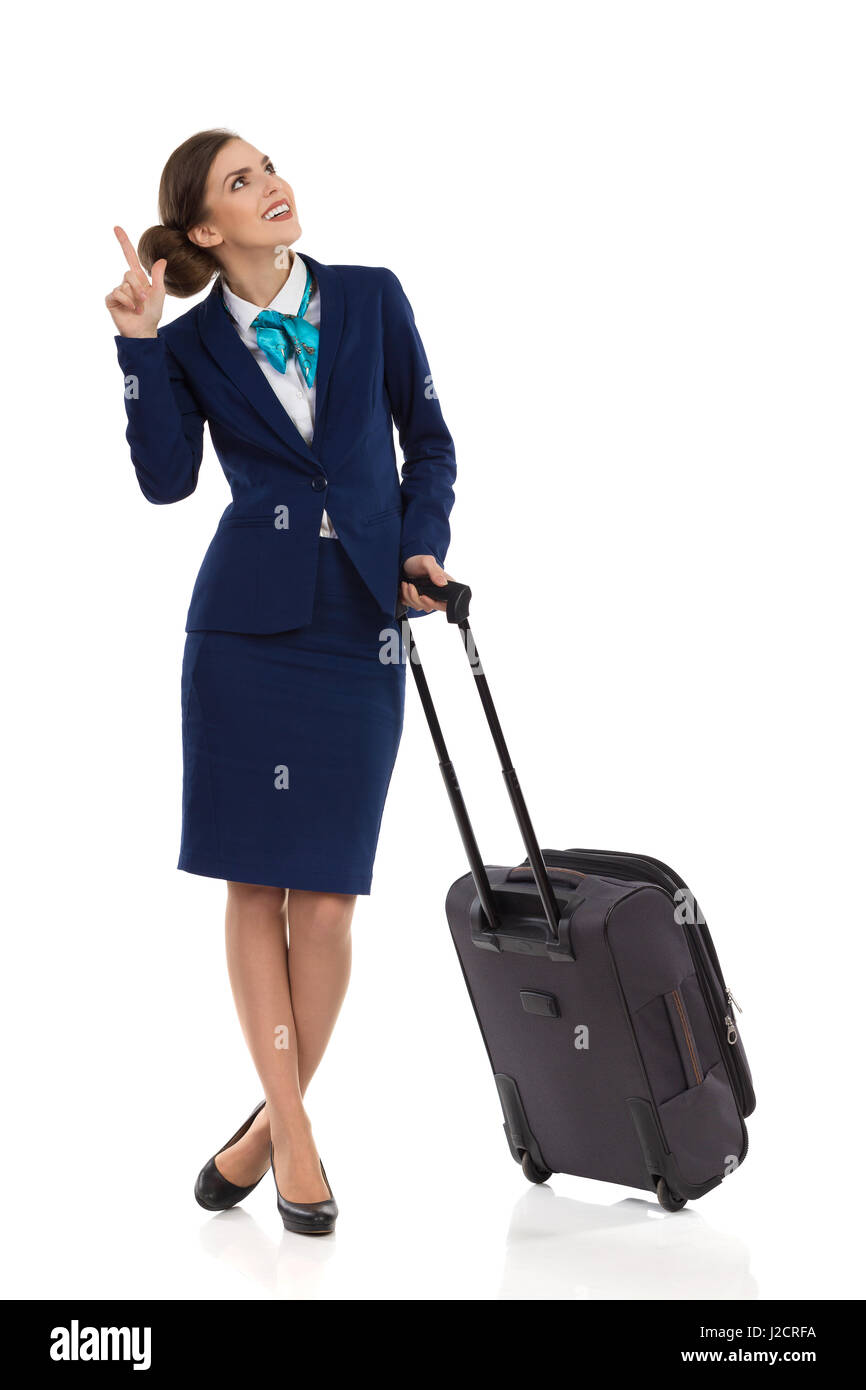 Smiling woman in formal blue suit and skirt standing with trolley bag, looking up and pointing. Full length studio - Stock Image