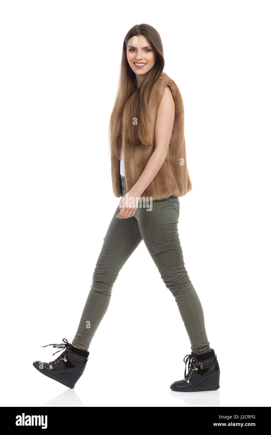 Young woman in brown fur waistcoat, khaki pants and black boots walking and looking at camera. Side view. Full length - Stock Image