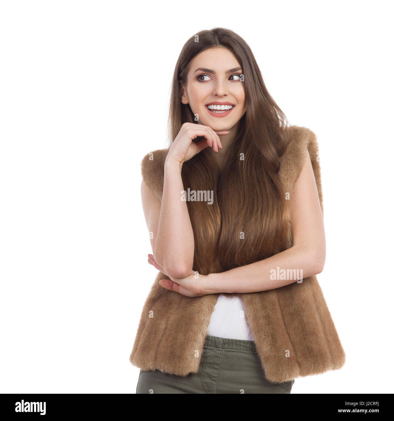 Beautiful young woman in brown fur waistcoat smiling and looking away. Waist up studio shot isolated on white. - Stock Image
