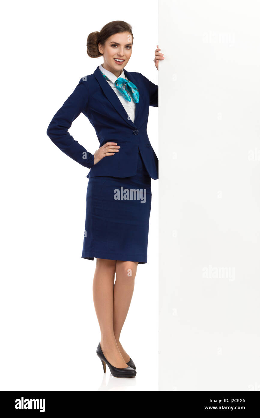 Young woman in blue formalwear and high heels, standing close to white wall, holding hand on hip and looking at - Stock Image