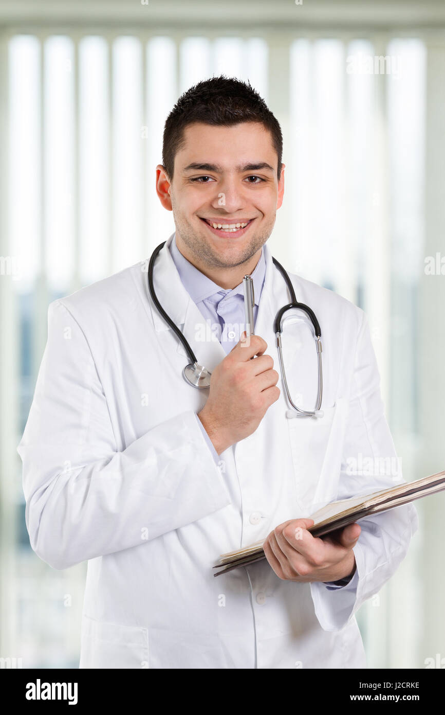 Doctor holding a pen and repotrts and smiling at you. - Stock Image