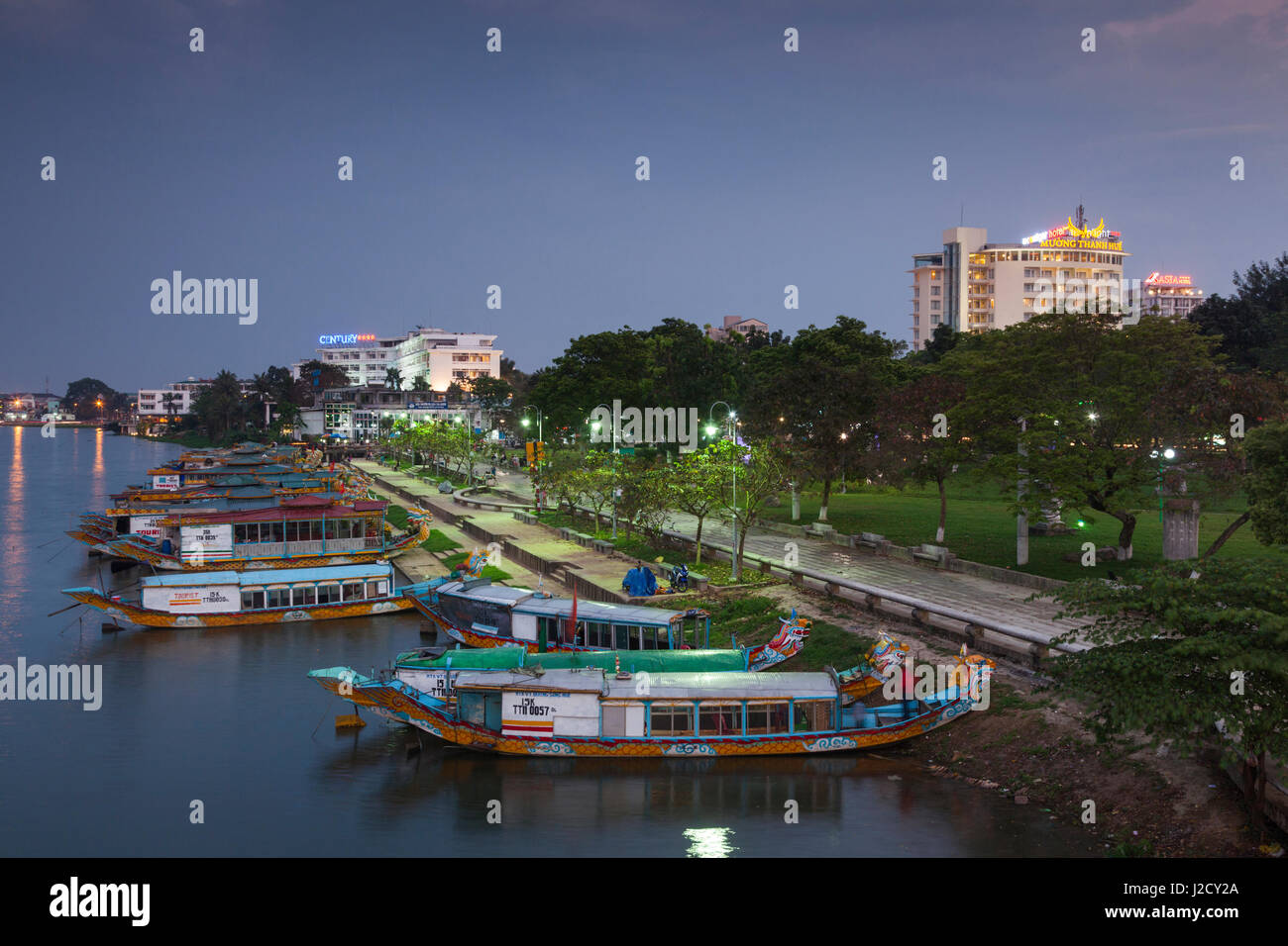 Vietnam, Hue. Elevated view of Century Hotel, Perfume river and dragon boats, dusk Stock Photo
