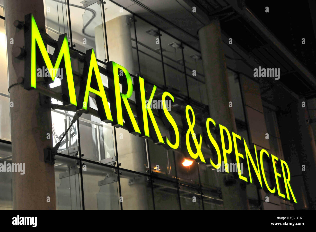 Night time illuminated Marks & Spencer uppercase store sign lettering on London England UK M&S store front - Stock Image