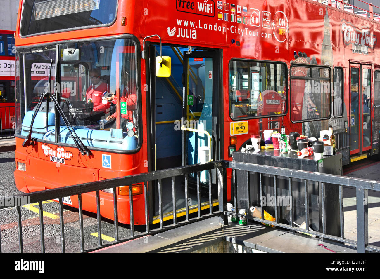 Red tour bus pulls up at bus stop on London Bridge beside pavement cabinet used as rubbish dump for coffee cups - Stock Image