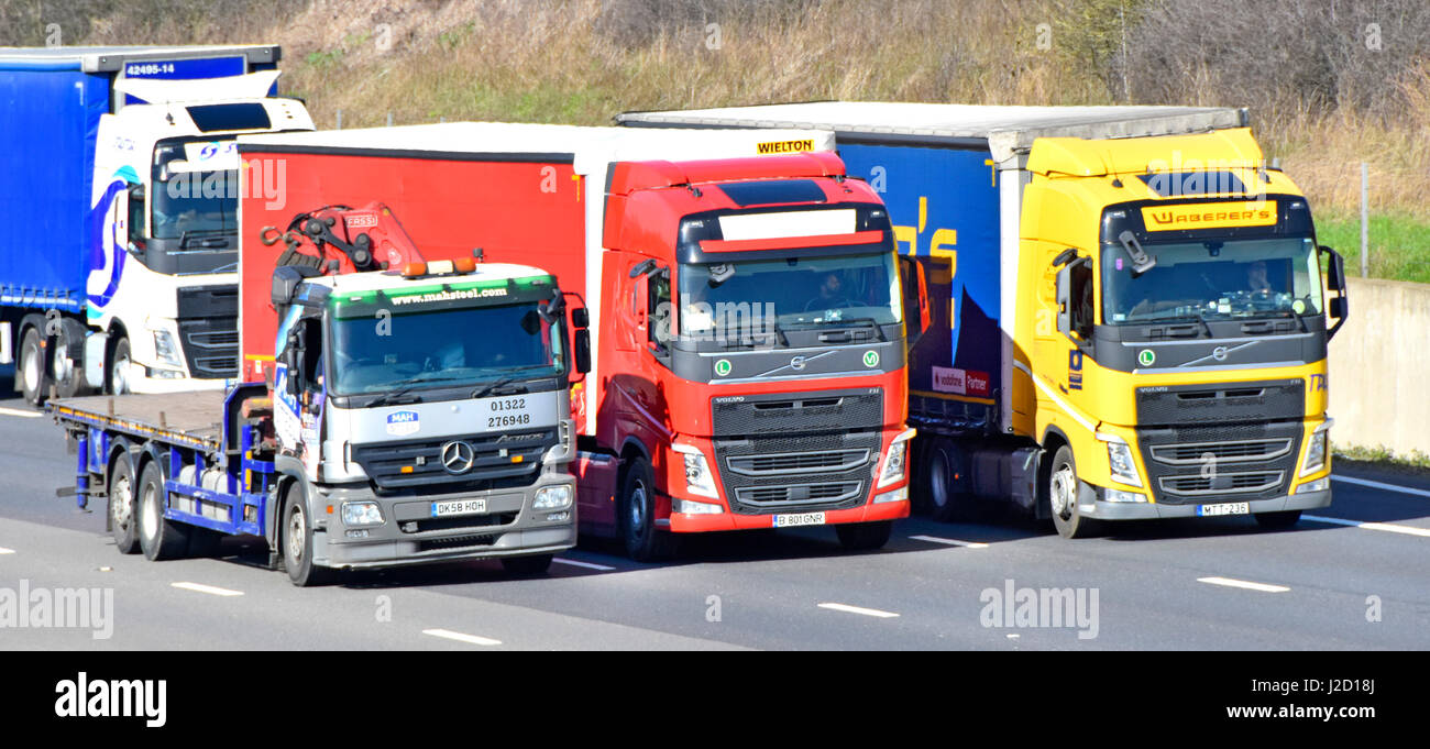 M25 motorway UK traffic truck lorry driver driving in lane three overtaking two foreign continental lorries in busy - Stock Image