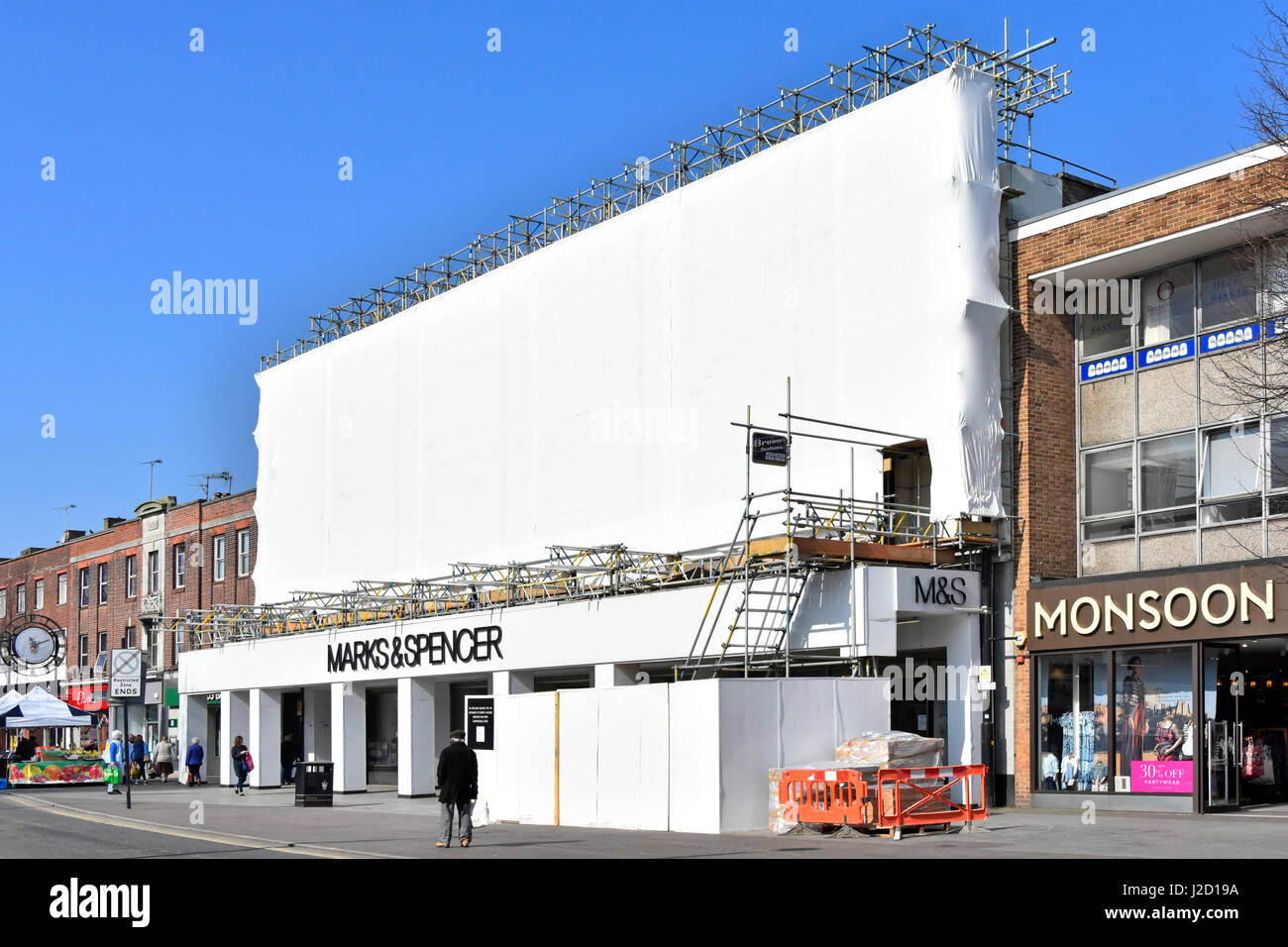 Scaffolding & plastic sheeting around front facade of open UK Marks and Spencer High Street store during building - Stock Image