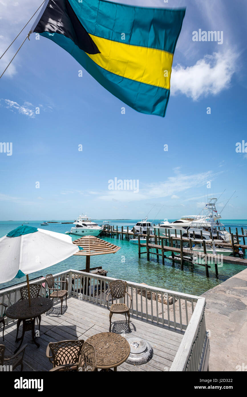 The Bahamian flag waves above the clear blue waters and