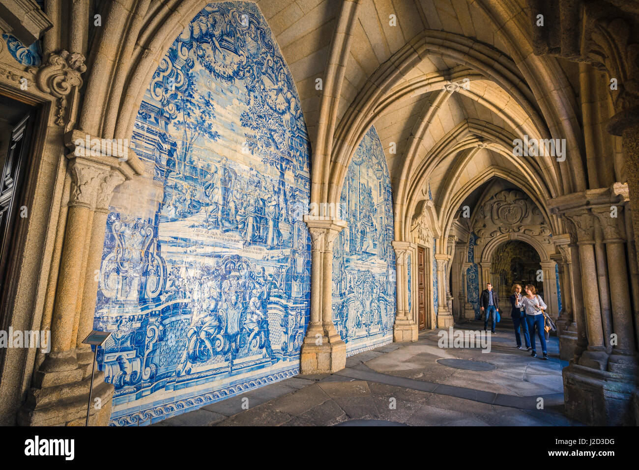 Porto Portugal azulejos, tourists look at a section of wall in the Baroque cathedral cloisters richly decorated - Stock Image