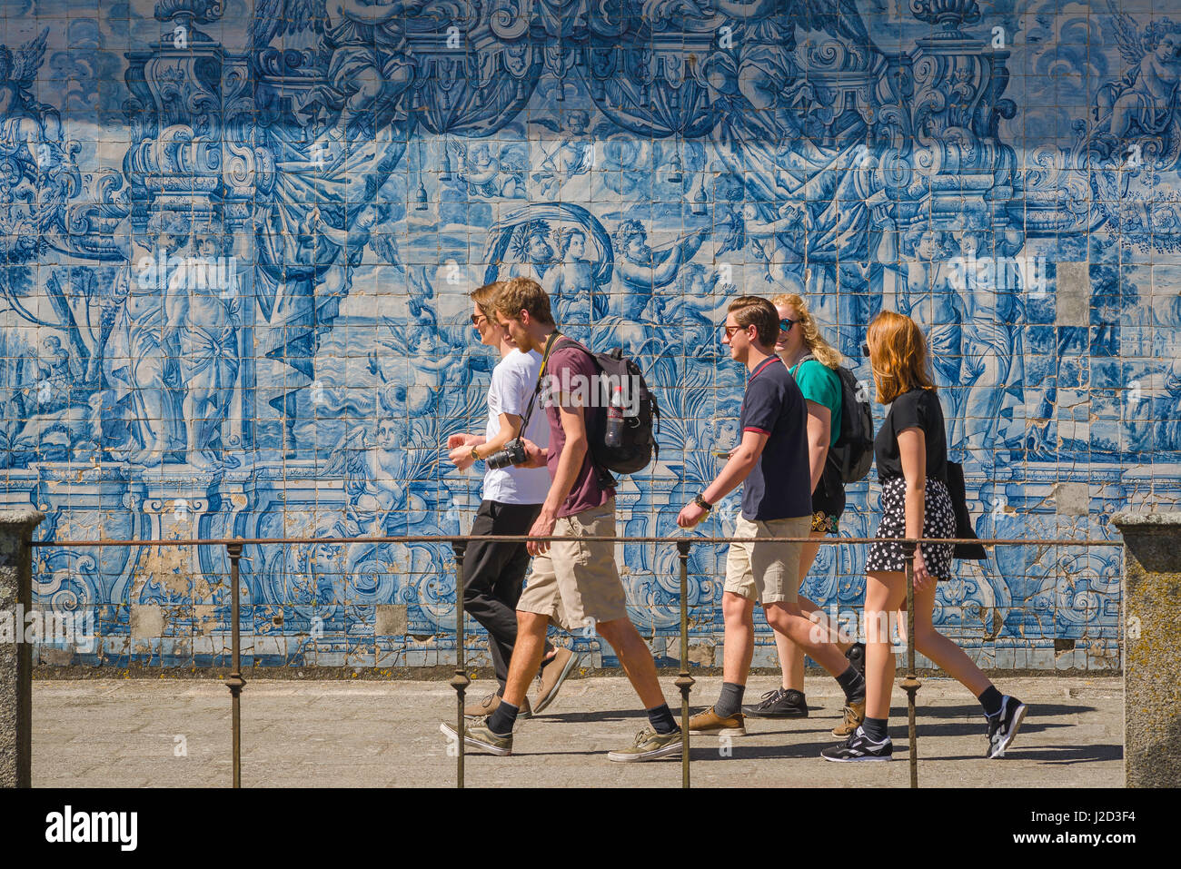 Porto Portugal azulejos, a group of young people walk past a wall in the Se cathedral cloisters decorated with blue - Stock Image