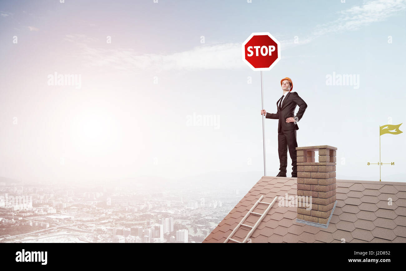 Caucasian businessman on brick house roof showing stop road sign. Mixed media - Stock Image