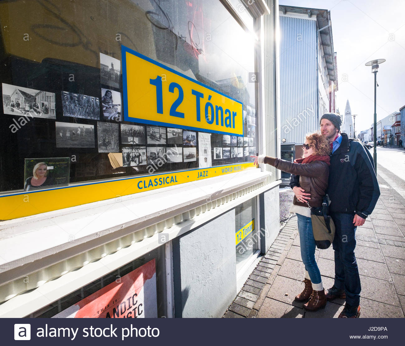 Young woman pointing to photographs in window of 12 Tónar record shop, Skólavörðustíg, - Stock Image