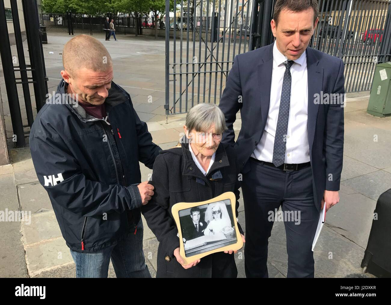 Teresa Watt, wife of Barney Watt, outside Belfast Coroner's Court with a photo of them on their wedding day, - Stock Image