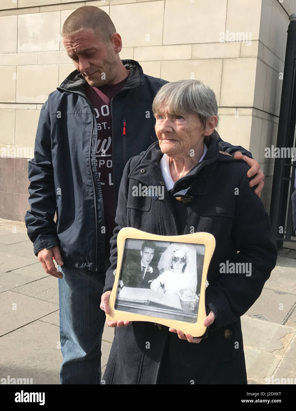 Teresa Watt, wife of Barney Watt, outside Belfast Coroner's Court with a photo of them on their wedding day - Stock Image