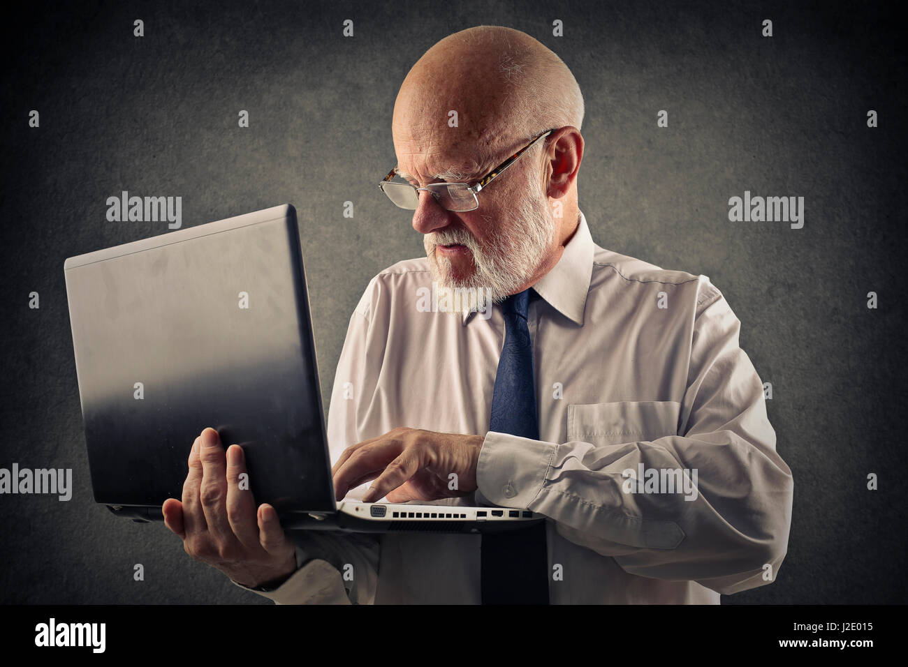 Old businessman working on laptop - Stock Image