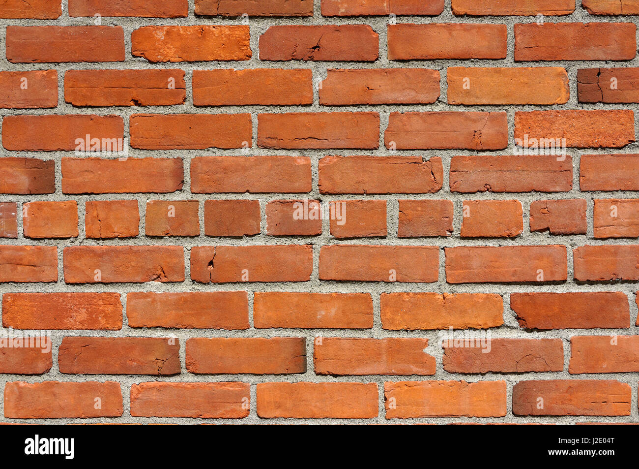 Close-up of a red brick wall with mortar - Stock Image
