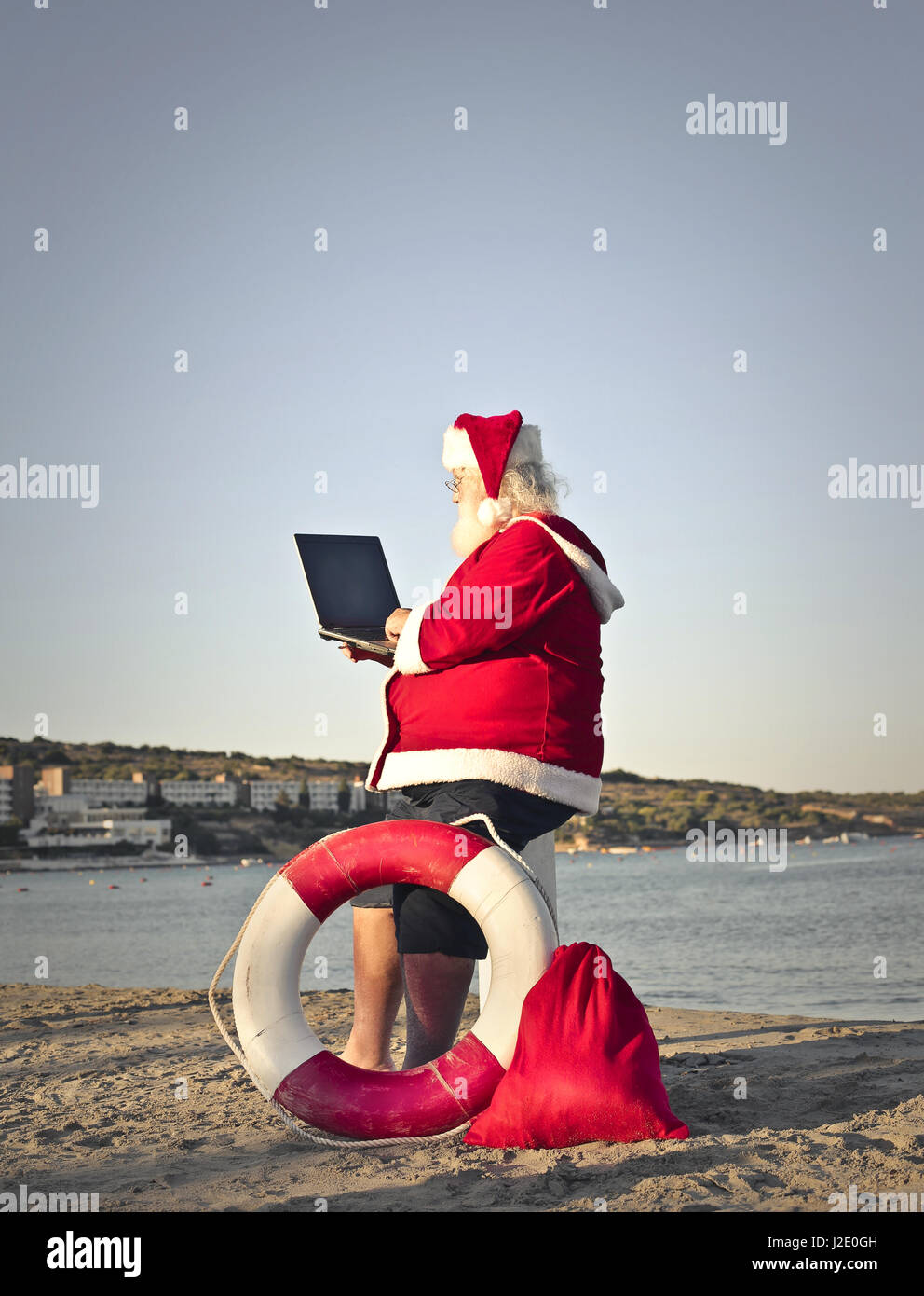 Santa with laptop outside - Stock Image