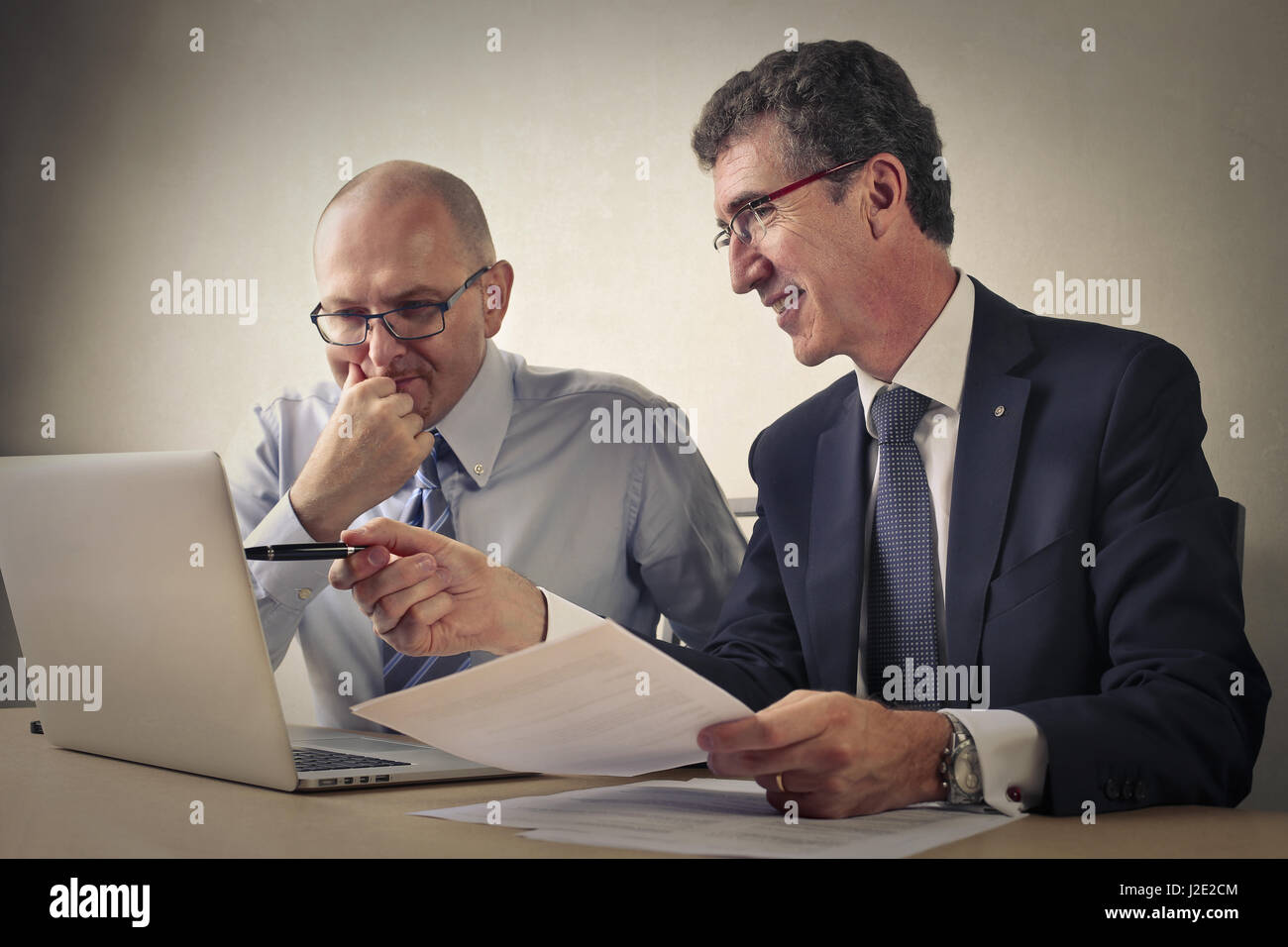 2 businessmen discussing and looking at tablet - Stock Image