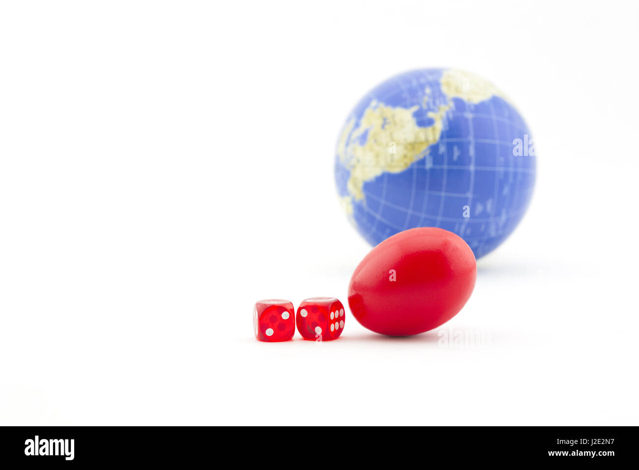 Dice and red nest egg with global background signify financial gamble and risks inherent in business, investment, - Stock Image